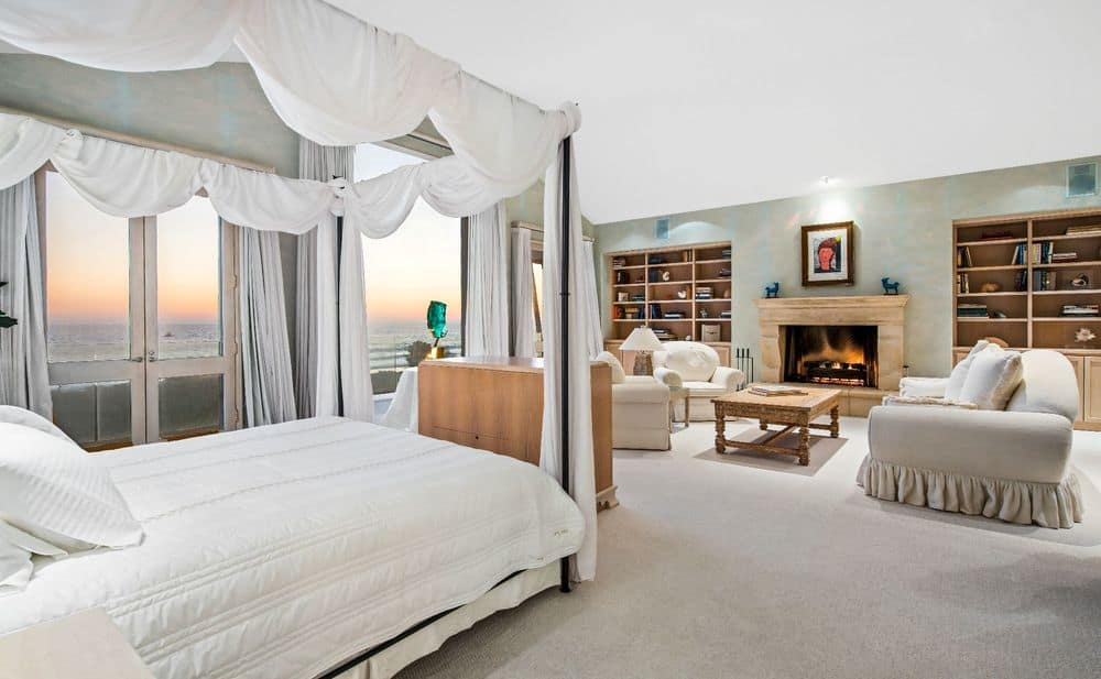 Large primary bedroom with a white bed set along with a personal living space with a fireplace.