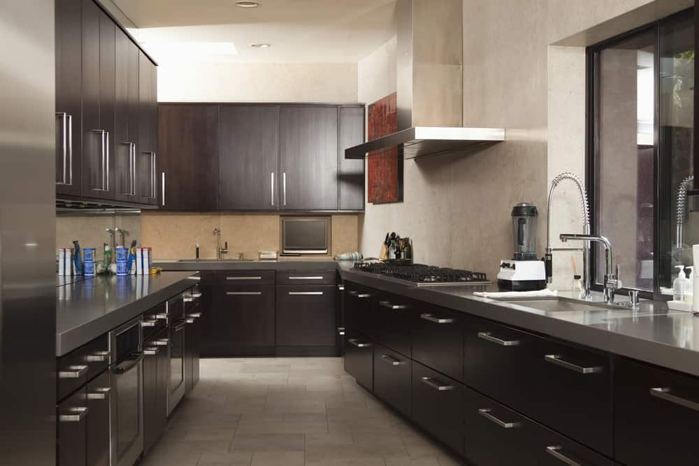 This is a charming galley kitchen with a narrow corridor in the middle flanked by dark brown modern cabinetry with stainless steel handles that match the grayish silver countertops as well as the stainless steel appliances and fixtures that are complemented by the gray walls and ceiling.