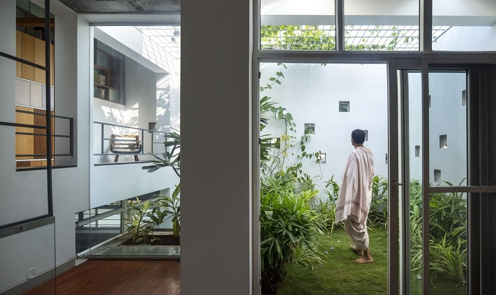 This is a close look at the indoor garden of the house with landscaping of a grass lawn, shrubs and creeping vines enhanced by the miniature windows and the open ceiling with grills.