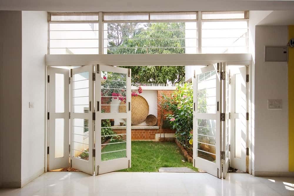 This is a look at the miniature garden of the back of the house with folding glass doors leading to the small grass lawn with shrubs and planters.