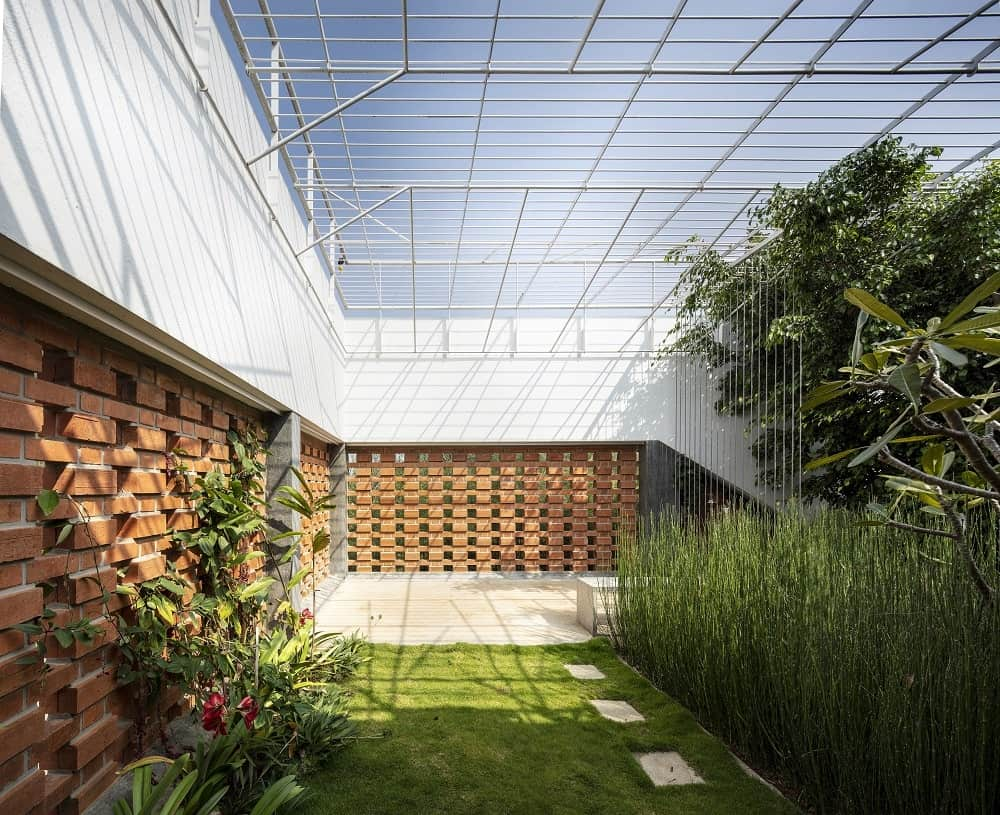 This is a close look at the indoor garden of the house with a glass ceiling supported by metal beams that bring natural lighting to the grass lawn, shrubs and trees complemented by the red brick walls.