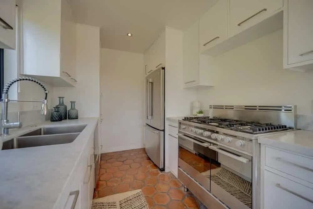 This is the kitchen with large stainless steel appliances that stand out against the light beige walls and terracotta flooring tiles.