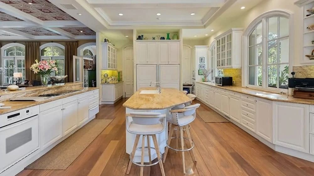 This is the large kitchen with hardwood flooring that matches the wood countertop of the kitchen island complemented by the bright cabinetry that matches the tray ceiling.