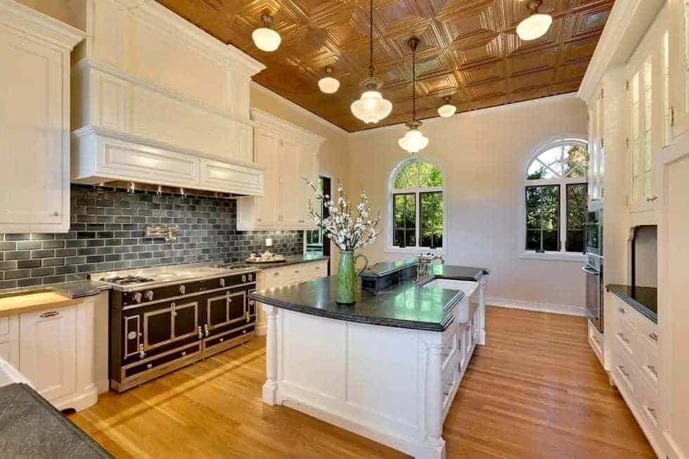 The kitchen has a large kitchen island that stands out against the hardwood flooring. It pairs well with the black cooking area and the white cabinetry.