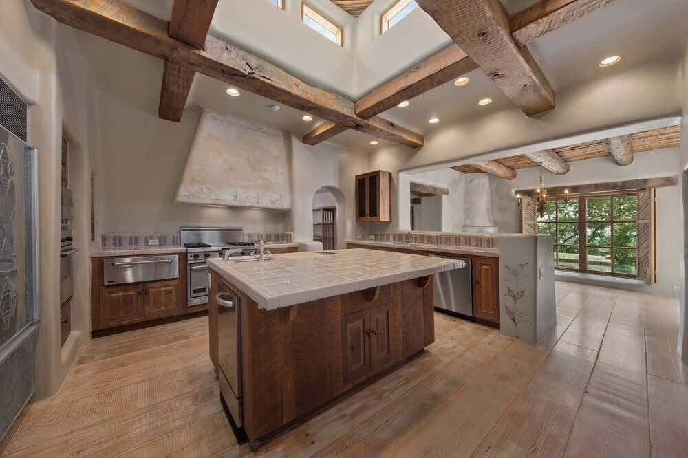 This is a view of the kitchen showcasing the thick exposed wooden beams of the ceiling surrounding the skylight above the kitchen island that has a wooden tone to match the cabinetry contrasted by the stainless steel appliances.