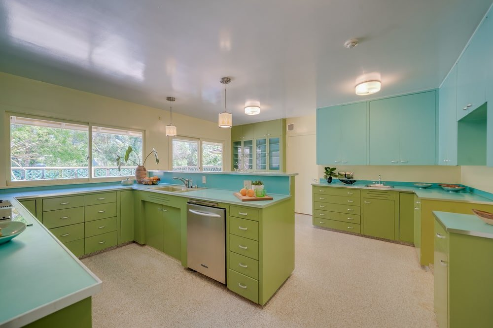 This is the kitchen that has lime green cabinetry lining the walls and the U-shaped peninsula. These are then complemented by pastel blue walls and bright ceiling.