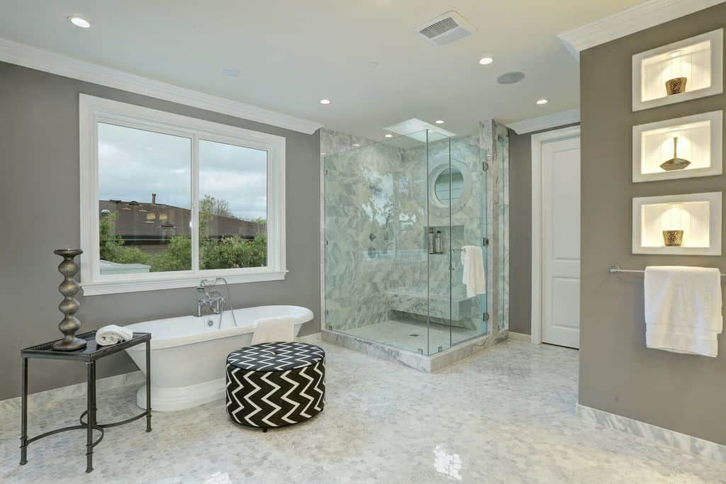 Primary bathroom with gray walls and stylish marble tiles flooring. It offers a walk-in shower room in the corner, along with a freestanding tub by the window.