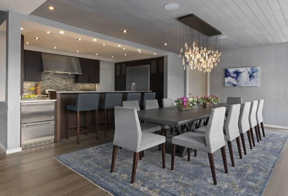 A cozy dining space across the bar boasting a gray dining table and upholstered chairs that sit on a blue area rug over the hardwood flooring. It is decorated with an abstract painting and glass cluster chandelier that hung from the shiplap ceiling.