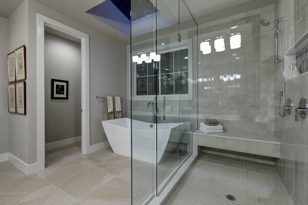 A floral gallery adds a nice accent in this primary bathroom with a toilet area and a freestanding tub underneath the skylight. It includes a walk-in shower with a tiled bench and chrome fixtures enclosed in frameless glass panels.