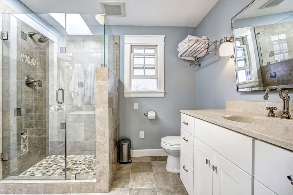 A stainless steel pot rack is fixed above the toilet facing the walk-in shower that's enclosed in frameless glass doors. There's a granite top vanity on the side fitted with chrome fixtures and hardware.