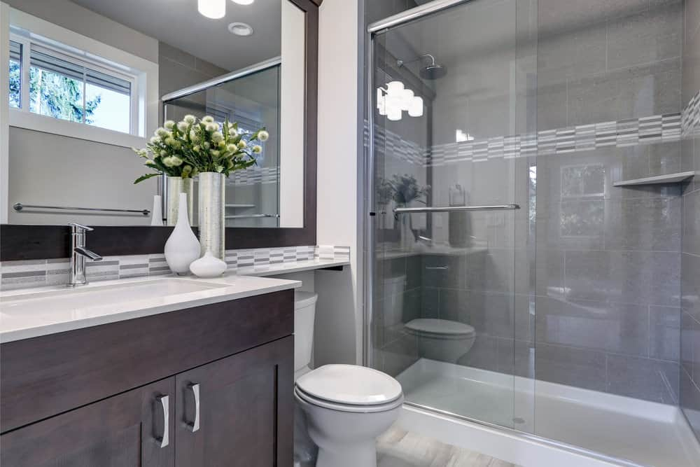 Sleek vases complement the dark wood vanity that's paired with a matching wall mirror. Next to it is the toilet and a walk-in shower that's clad in gray brick tiles with a linear mosaic accent.