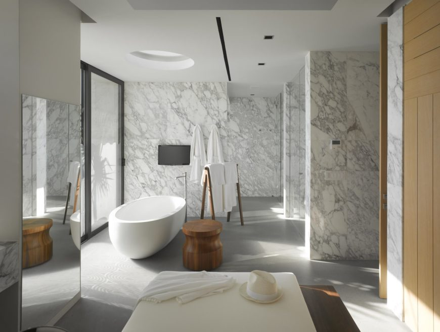 Gray marble walls run throughout this primary bathroom with a walk-in shower and a freestanding tub underneath a round skylight. It is complemented by a wooden towel rack and stool along with a white ottoman across the full-length mirror.