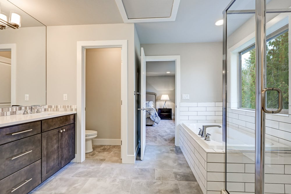 A white door opens to this primary bathroom showcasing a toilet area and a dark wood vanity that's paired with a frameless mirror mounted with glass sconces. There's a deep soaking tub on the side that's clad in white subway tiles extending to the backsplash.