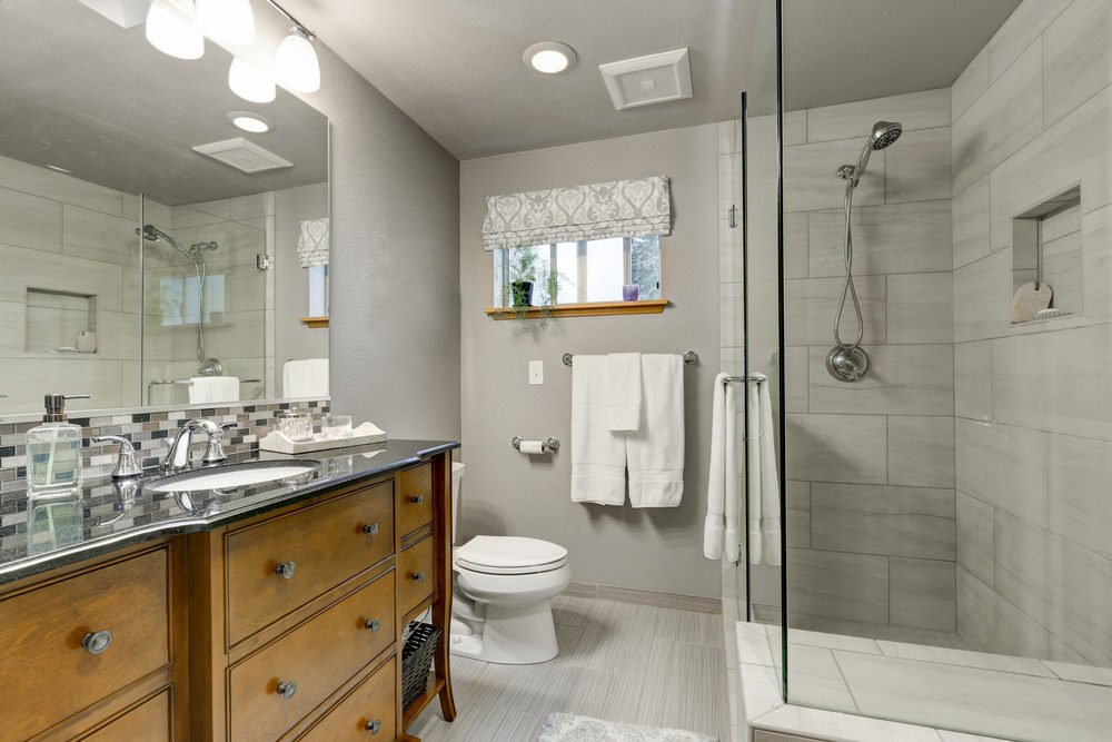 Gray primary bathroom with stripe tile flooring and a picture window dressed in a patterned roman shade. It includes a walk-in shower and a toilet along with a wooden vanity that's topped with an undermount sink and granite countertop.