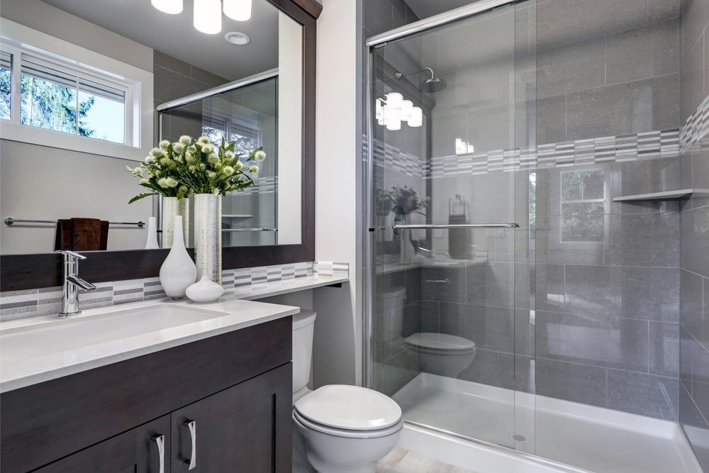 Glass sconces reflected in the glass sliding door of the walk-in shower illuminate the wooden framed mirror and dark wood vanity that's situated next to the toilet.