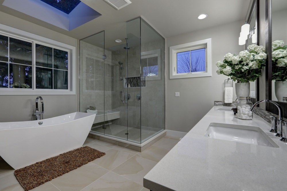 A brown shaggy rug complements the freestanding bathtub by the white framed window and underneath a skylight. It is accompanied by a walk-in shower and a dual sink vanity against the light gray walls.