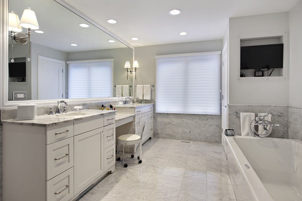 This primary bathroom offers a drop-in tub and a large dual sink vanity that's paired with a cushioned glass chair over gray marble tiled flooring. It includes a wall mount TV and a rectangular mirror mounted with classic sconces.