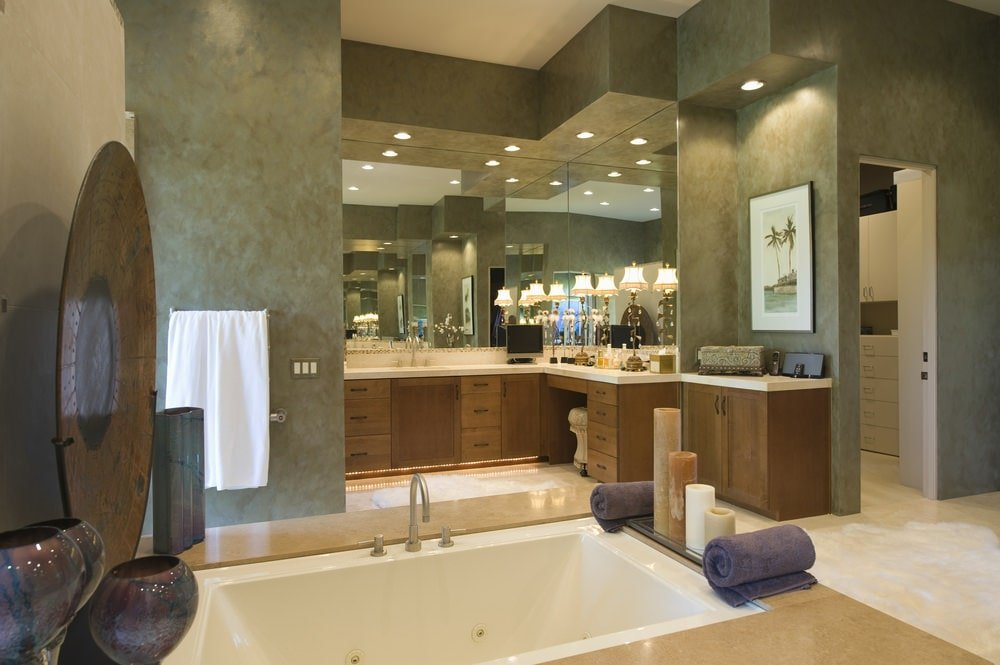 Warm primary bathroom designed with a landscape artwork and antique decors that sit on a deep soaking tub fitted with a gooseneck faucet. It is complemented with wooden vanities that are illuminated by lovely lampshades and recessed lights.
