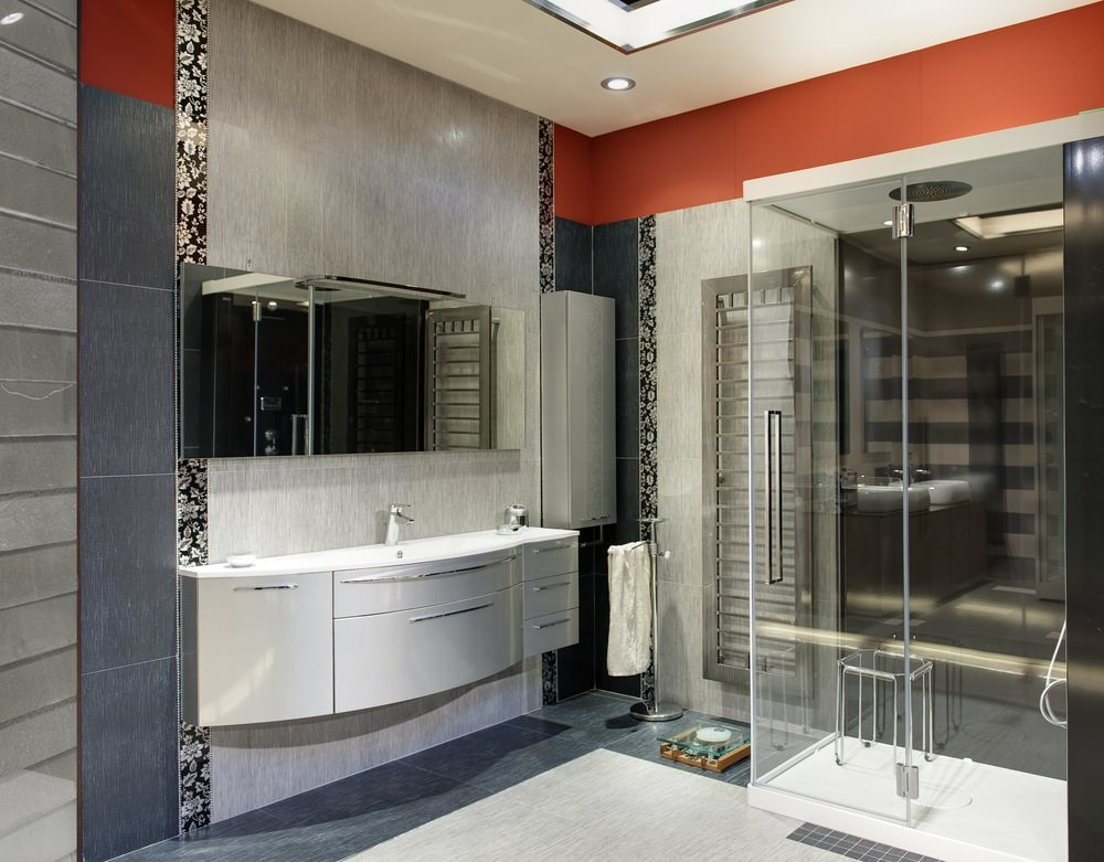 Red and black floral panels add a gorgeous accent in this gray bathroom with a floating sink vanity and a walk-in shower that's filled with a glass stool and chrome fixtures.