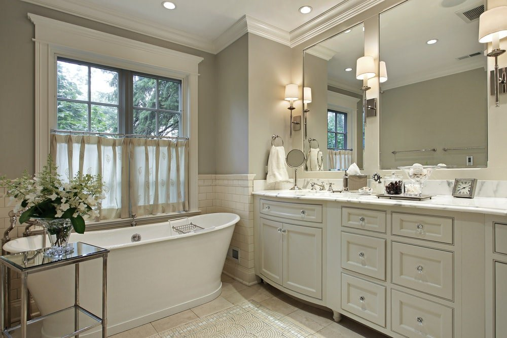 A chrome shelving unit topped with a glass flower vase sits in front of the freestanding tub by the framed windows dressed in leaf patterned valances. It is accompanied by frameless mirrors illuminated by classic sconces along with a white vanity that's fitted with glass knobs.