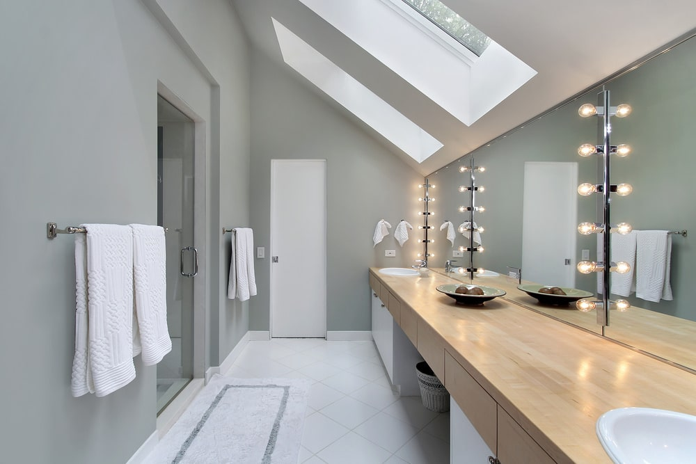 Gray primary bathroom with a shower area and a large vanity accented with frameless mirrors that are mounted with bulb lights. It has white tiled flooring and a shed ceiling fitted with skylight windows.