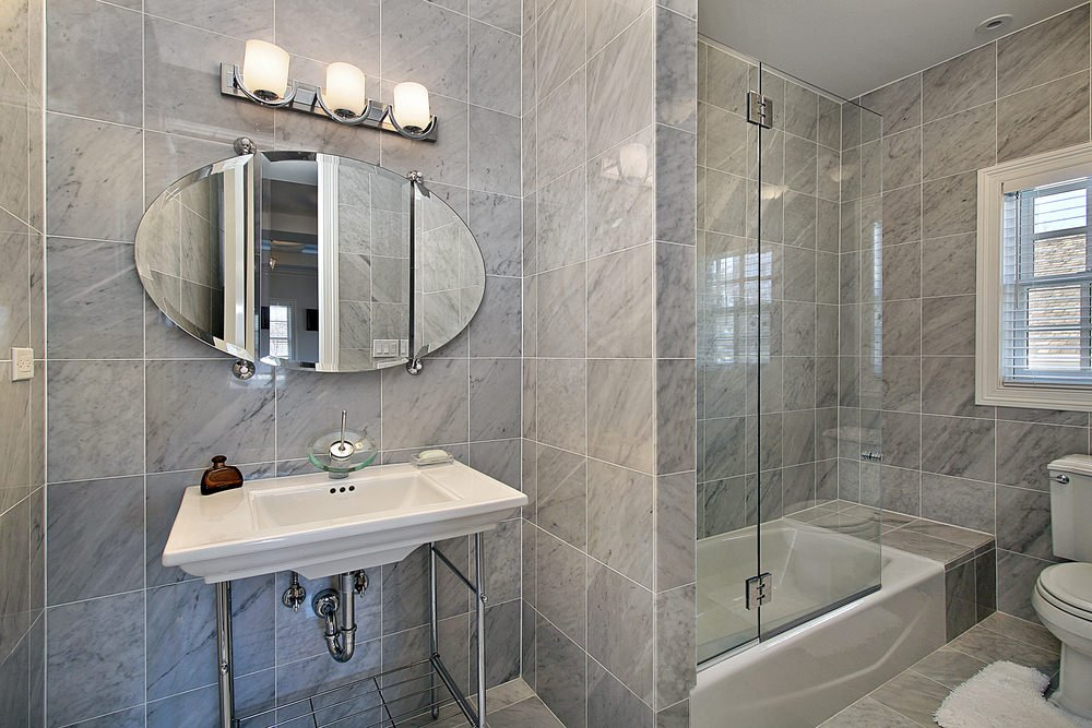 This primary bathroom features a shower and tub combo along with a traditional toilet that's complemented by a white shaggy rug. It includes a sink pedestal with a chrome base and an oval mirror lighted by glass sconces.