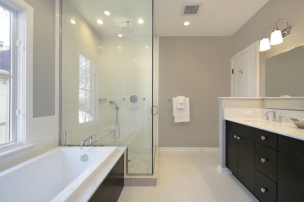 Bright primary bathroom with a deep soaking tub and dark wood vanity illuminated by glass sconces. It includes a walk-in shower that's filled with a tiled bench and chrome fixtures.