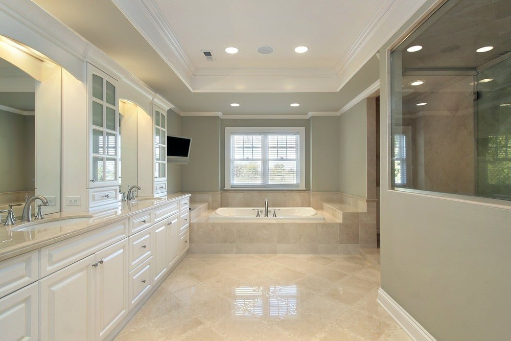 Gray primary bathroom filled with a walk-in shower and an immense vanity along with a drop-in tub by the white framed window. It has beige tiled flooring and a tray ceiling mounted with recessed lights.