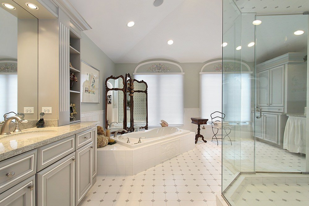 Spacious primary bathroom with a walk-in shower and a gray vanity with white trims blending in with the walls. It includes a deep soaking tub that's complemented by a three-panel mirror and metal chair with a wooden table on the side.