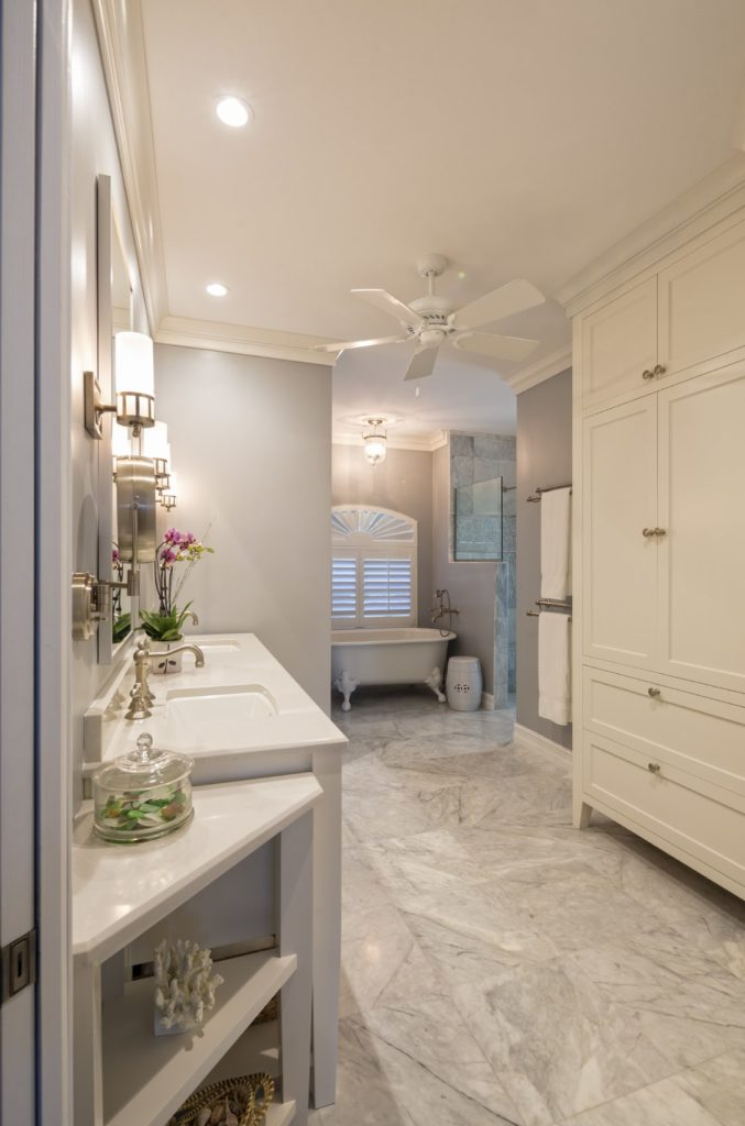 Classic primary bathroom offers a full height cabinet and a dual sink vanity with corner shelving on the side. There's a clawfoot tub by the louvered window sitting next to the walk-in shower over marble flooring.