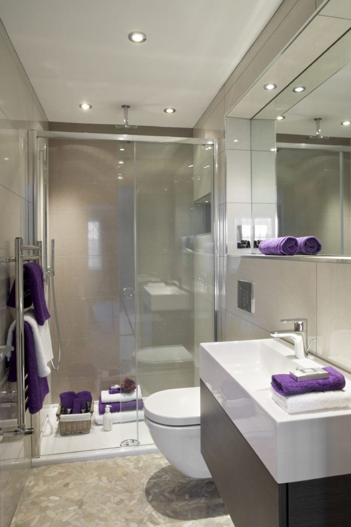 Purple towels stand out in this gray bathroom with a stainless steel wall mounted rack and a modern toilet flanked by a walk-in shower and trough vanity.