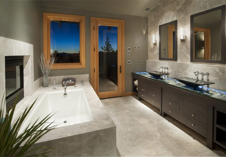 Dark wood vanity with a river rock countertop and vessel sinks is the highlight of this primary bathroom boasting a deep soaking tub and a fireplace that's fixed against the gray wall.
