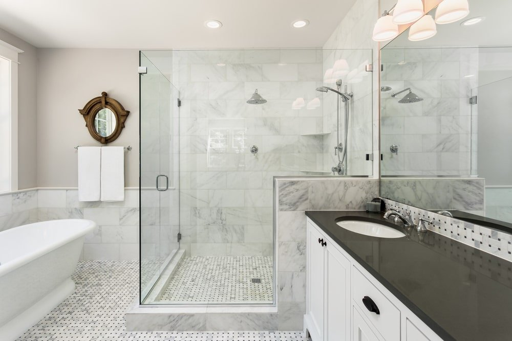 An architectural mirror hangs above the chrome towel rack facing the freestanding tub over the marble tiled flooring. It is accompanied by a walk-in shower and a white vanity contrasted by a black granite countertop and wrought iron hardware.