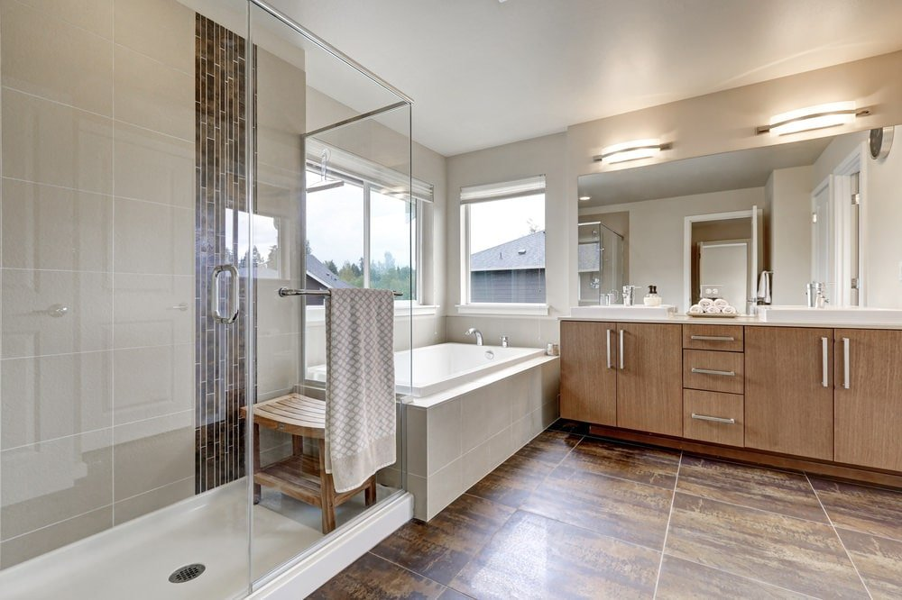 Linear sconces illuminate the frameless mirror and wooden vanity that's fitted with dual sink and chrome pulls. It is adjacent to the deep soaking tub and a walk-in shower with a wood plank seat.