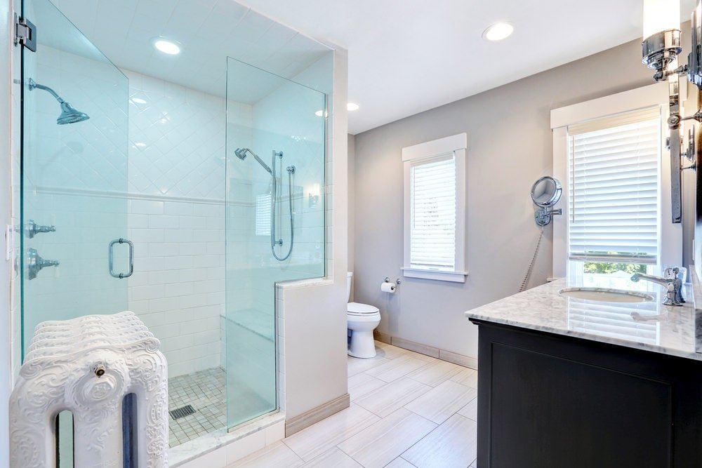 Dark wood vanity with marble countertop faces the walk-in shower that's complemented by a white rack designed with intricate details. There's a toilet on the side concealed with light gray walls.