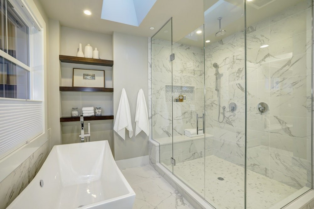 Sleek primary bathroom with inset shelving and a freestanding tub by the glazed window facing the walk-in shower with a tiled bench. It has marble flooring and a regular white ceiling fitted with skylight.