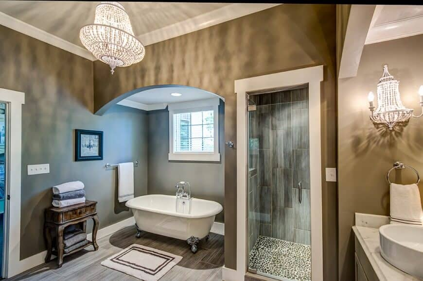 Ambient light from the beaded chandelier and wall sconce creates a warm and cozy feel in this primary bathroom boasting a vessel sink vanity and a walk-in shower along with a clawfoot tub that's accompanied by a bordered rug and a wooden table.