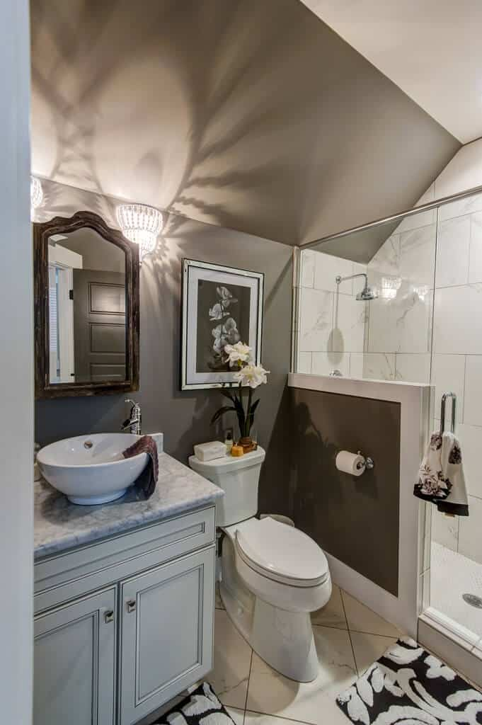 This gray bathroom is decorated with floral artwork and an arched mirror mounted above the vessel sink vanity lit by beaded sconces. It has a walk-in shower and a toilet over marble tiled flooring topped by black printed rugs.
