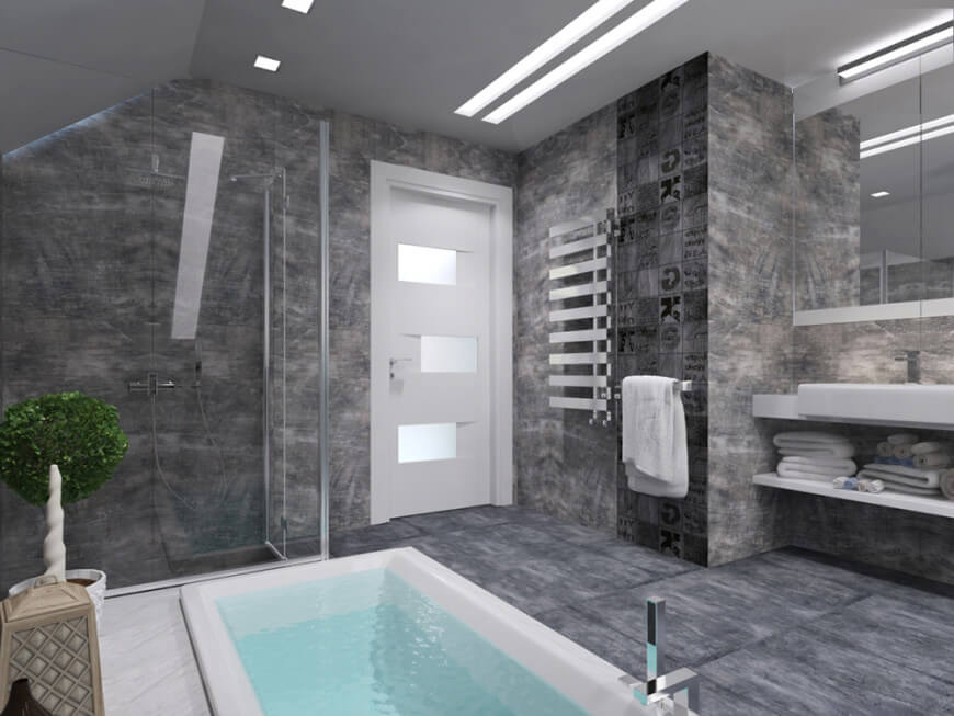 Sleek primary bathroom with a vaulted ceiling and a white door fitted with glass insets. It features a walk-in shower and a deep soaking tub facing the floating vanity that's paired with frameless mirrors.