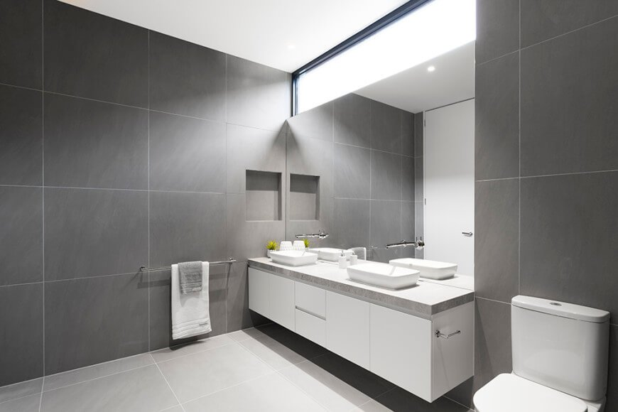 Natural light streams in through the glazed window that's fixed above a frameless mirror. This gray bathroom showcases a traditional toilet and a floating vanity with a marble countertop and a pair of vessel sinks.
