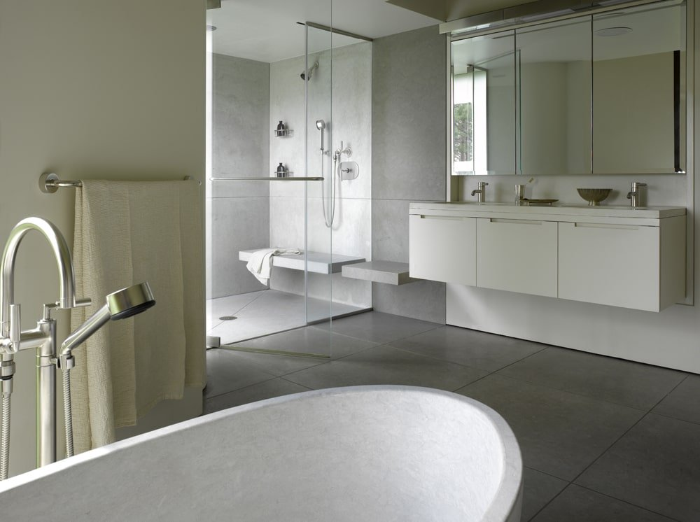 Neutral primary bathroom with a freestanding tub and a walk-in shower filled with a built-in sink and chrome fixtures. It includes a floating vanity under the mirrored medicine cabinets lighted by linear sconces.