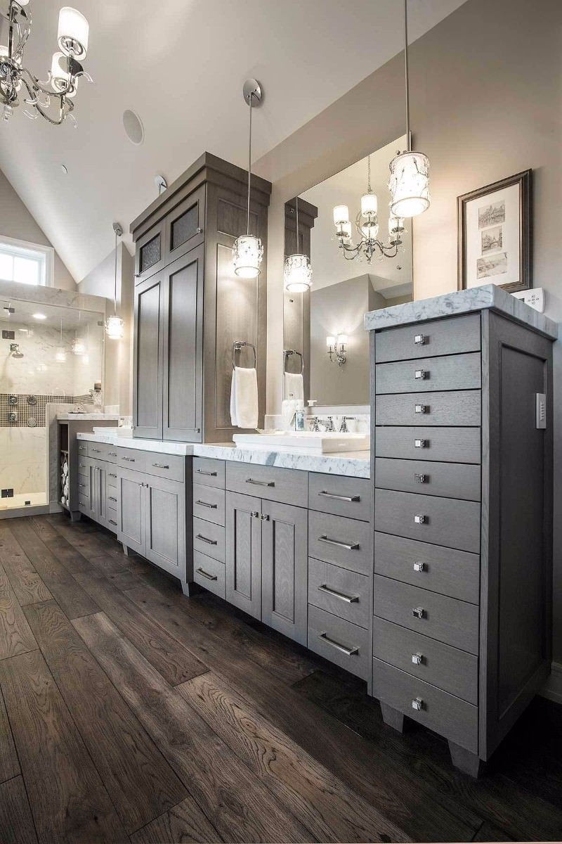 Glass pendant lights and a chrome chandelier that hung from the cathedral ceiling illuminates this primary bathroom featuring a walk-in shower and an immense vanity with marble countertop and semi-recessed vessel sinks.