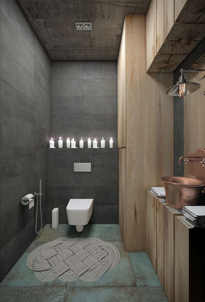 Small bathroom with gray tiled walls and a distressed green flooring topped by a lovely woven rug. It is filled with a wall hung toilet and a wood plank vanity that's topped with a copper vessel sink and a matching fixture.