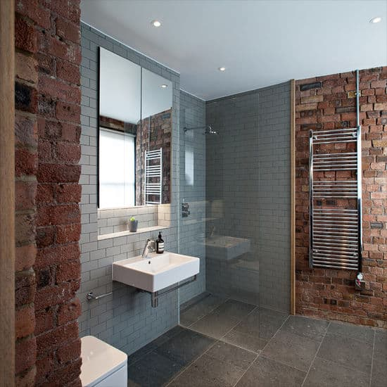 Red brick walls add texture in this gray bathroom showcasing a small shower area and a wall-mounted sink paired with a mirrored medicine cabinet that's fixed against the inset wall.