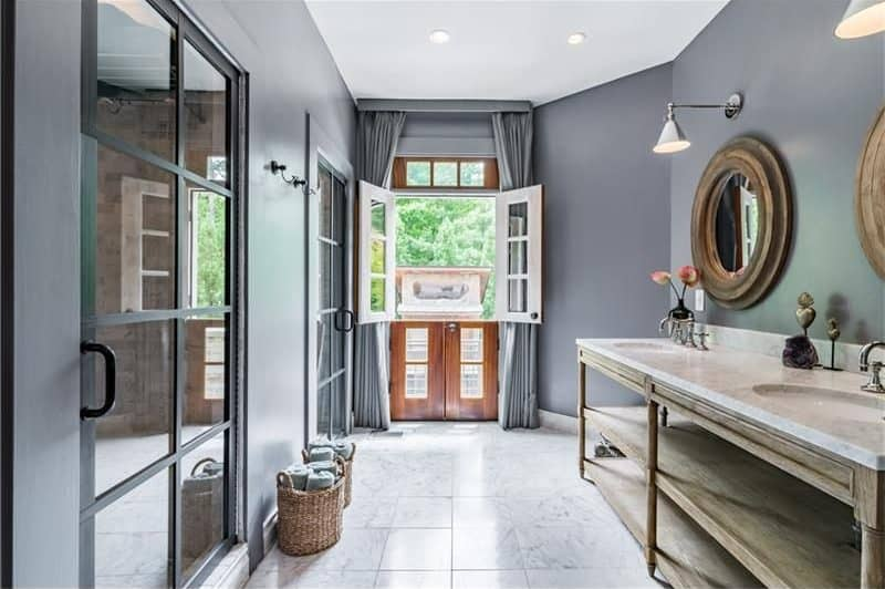 Gray primary bathroom offers round mirrors and a wooden vanity with dual sink and marble countertop matching with the tiled flooring. It includes a dutch double door that leads out to the balcony.