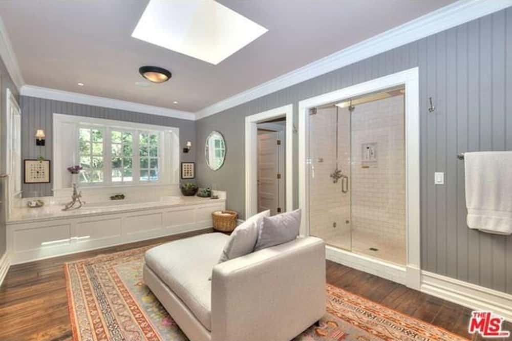 This primary bathroom boasts a walk-in shower and a deep soaking tub facing the cozy chaise lounge on a red printed rug underneath the skylight. It has wide plank flooring and gray beadboard walls mounted with a round mirror along with a pair of sconces and artworks.