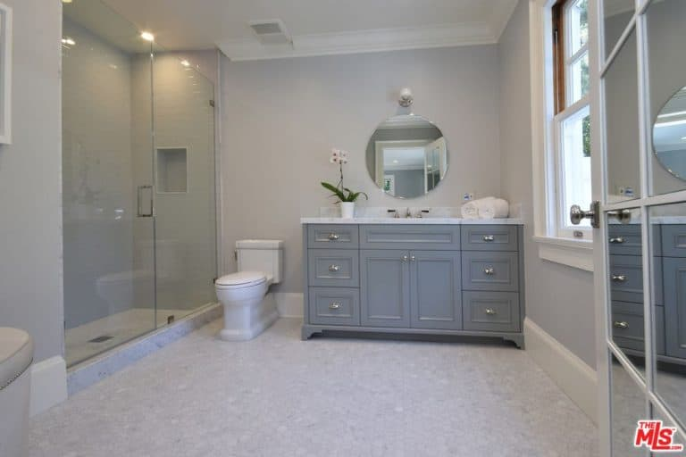 A mirrored door opens to this primary bathroom with a walk-in shower and a traditional toilet that sits on hex tile flooring, It includes a gray vanity paired with a round mirror that's fixed against the gray walls.