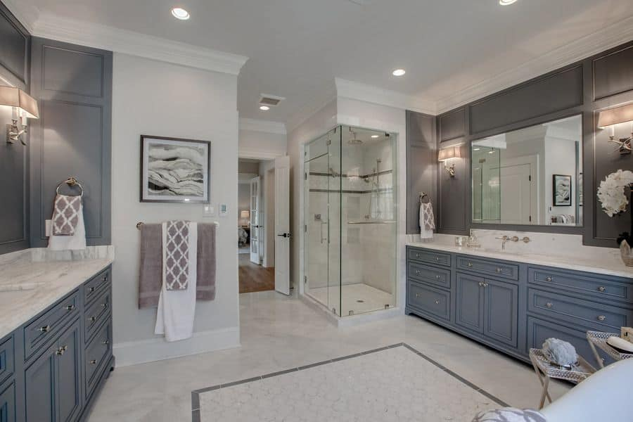 Sophisticated primary bathroom offers a walk-in shower and facing vanities lighted by sleek sconces that are mounted on the gray paneled walls. It has marble flooring and white walls adorned by a black framed artwork.
