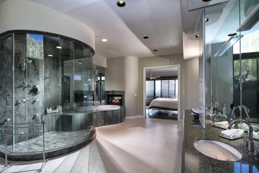 Contemporary primary bathroom with dual sink vanity and a sleek walk-in shower attached with a deep soaking tub. There's a fireplace fixed on the gray wall that adds warmth to this room.