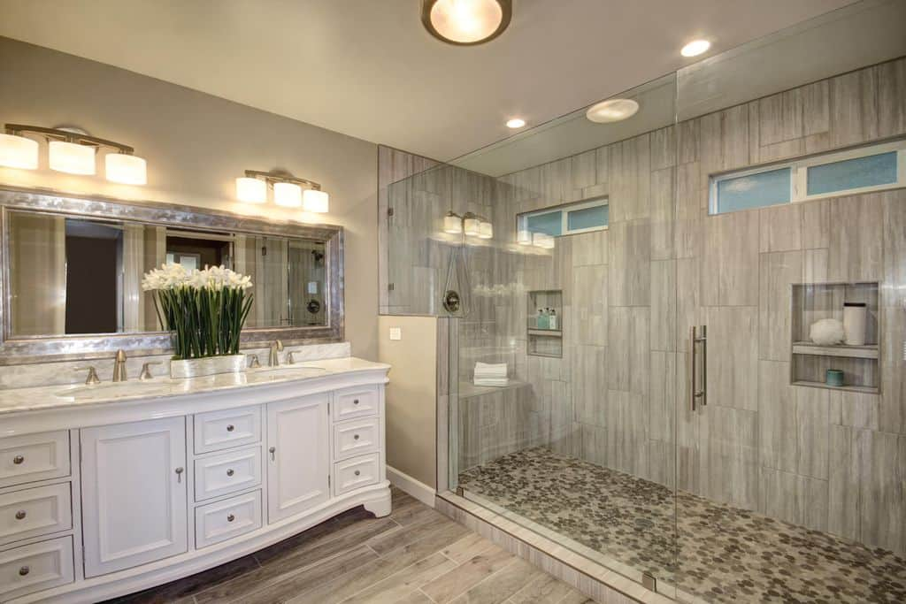 A rectangular mirror is fixed above a marble top vanity that sits next to the walk-in shower with inset shelves and a tiled bench. It is illuminated by glass sconces along with a flush mount light.